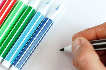 Hand writes on a white sheet next to lying colored markers Stock Photo