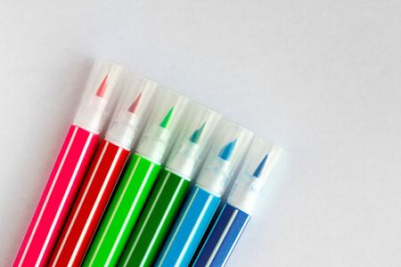 bunch of multi-colored felt pens on white blank sheet of paper