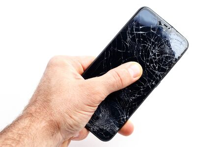 Hand holds a broken smartphone on a white background