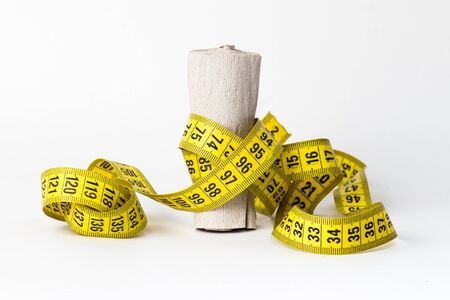 Measuring Tape wrapped around a roll of toilet paper diet concept Stock Photo
