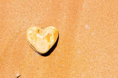 A heart-shaped stone lies on the sand as a symbol of love.