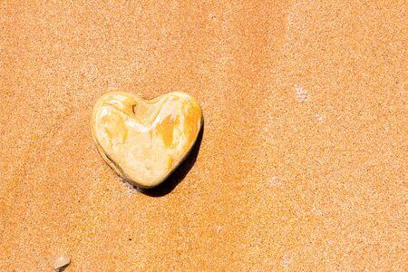 Una piedra en forma de corazón yace en la arena como símbolo del amor.