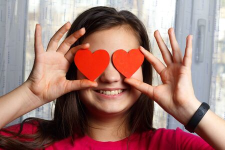 Girl holds two red hearts near her eyes as a symbol of love. Фото со стока