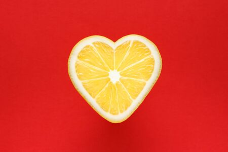 Yellow lemon in the shape of a heart on a red background.