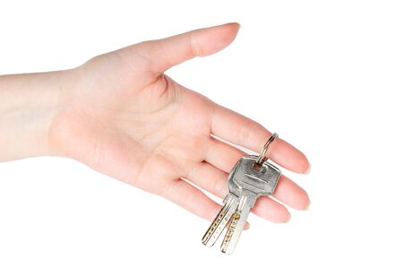 House keys in the female hand on a white background