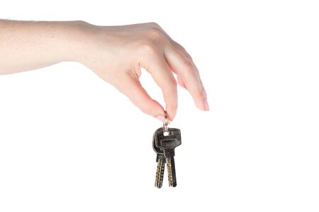 Female hand holds the keys to the apartment or from the house on a white background