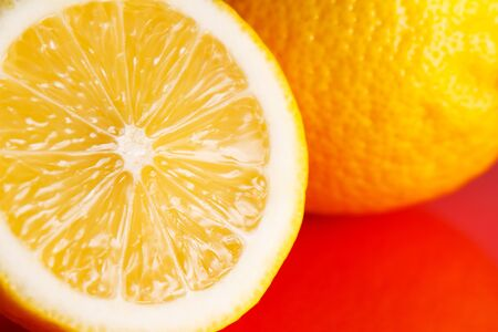 Half a lemon lies on a red background.