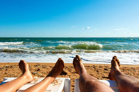 Legs of man and woman resting on the beach in front of the sea.