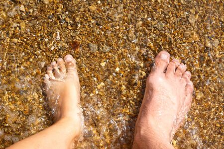 Legs of dad and daughter stand in sea water. Imagens - 150128294