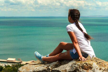 Beautiful young girl sits enjoying the sea view.