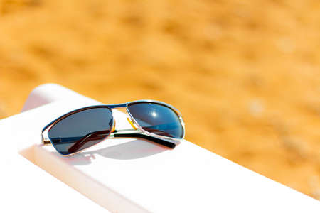 Sun glasses lie on sun loungers on the beach on a bright sunny day.