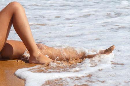 Womans legs splashing in clear sea water 版權商用圖片