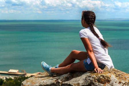 girl sitting enjoying sea view Imagens - 150931578