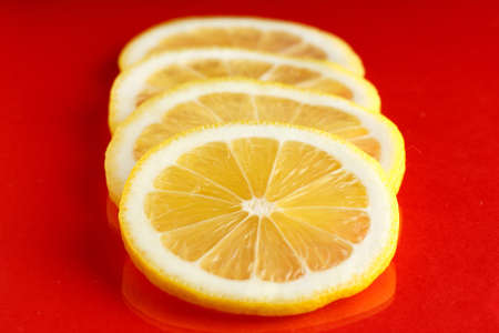 Slices of ripe bright lemon on a red background.