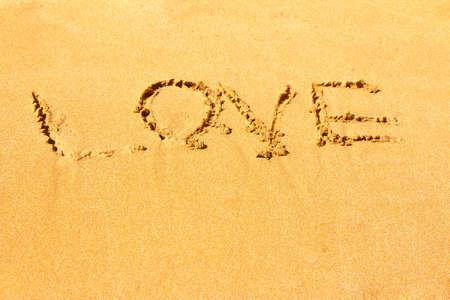 The inscription love on the sea sandy beach