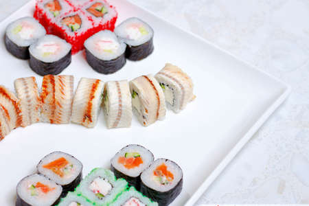 set of different types of sushi on a white plate