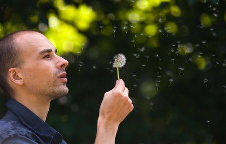 blowing dandelion: Man blowing dandelion