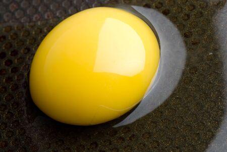 broken egg on a black frying pan. closeup Stock Photo - 5339669