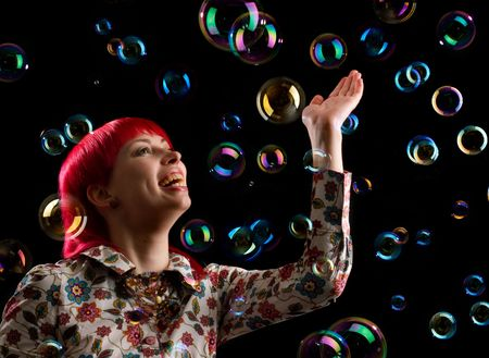 Portrait of a beautiful young woman with soap bubbles photo