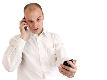 A businessman looks shocked while talking on his cell phone photo