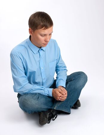 wistful:  Wistful youngl man sitting Stock Photo