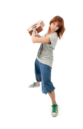 Girl smashing a guitar. Isolated on white photo