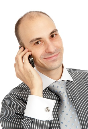 Closeup portrait of a happy young guy speaking on cellphone against white background photo