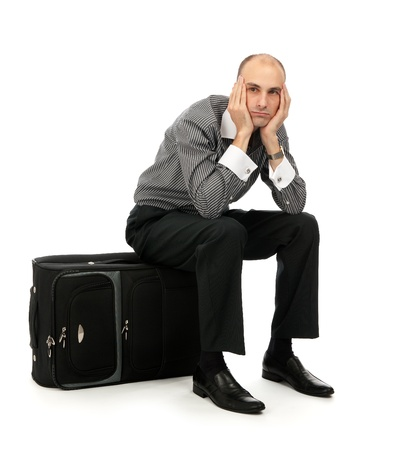 sitting on floor: Handsome young man sitting on his luggage