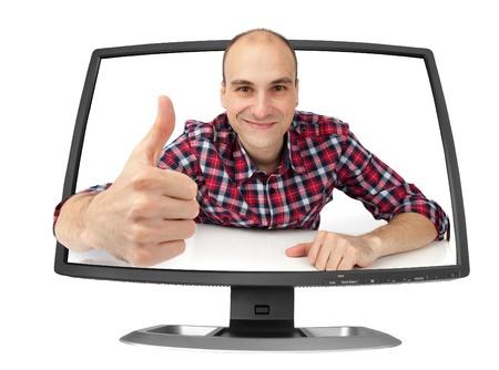 幸せの若い男が彼の親指をコンピューター モニターに表示