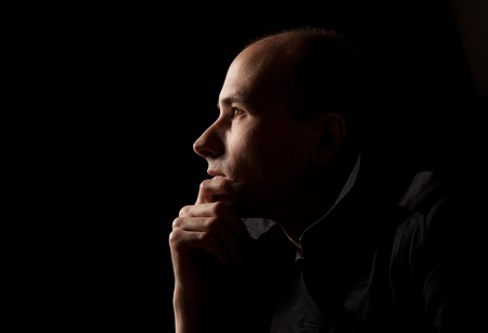 Portrait of young man thinking, black background Stock Photo - 9359492