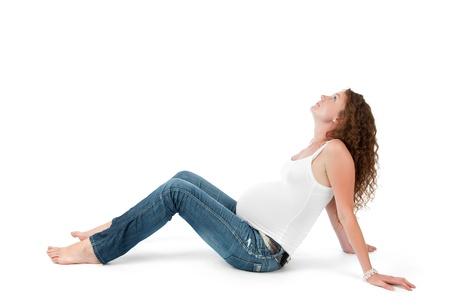 Pregnant woman doing gymnastic exercises on isolated white background photo