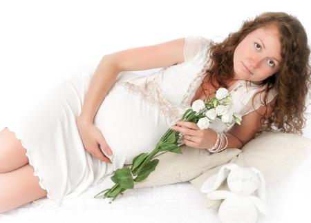 Pregnant young woman lies photo