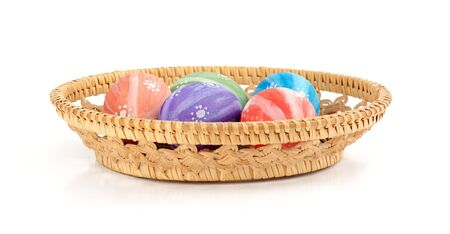 Easter colored eggs in the basket on white background photo