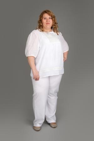 mujer gorda: sonriente mujer gorda sobre fondo gris