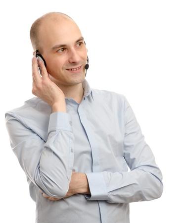 operador de servicio al cliente guapo que llevaba un auricular aislada en el fondo blanco Foto de archivo