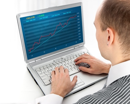 young man working of a laptop with Financial diagram photo