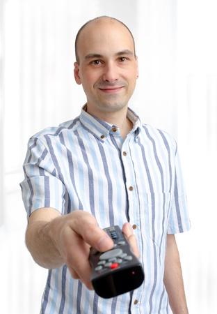 bald man: hombre joven con un control remoto de TV Foto de archivo