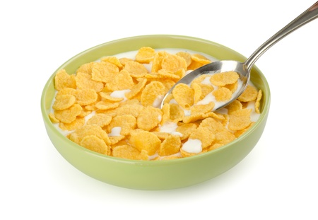 Bowl of corn flakes with milk and spoon isolated on white
