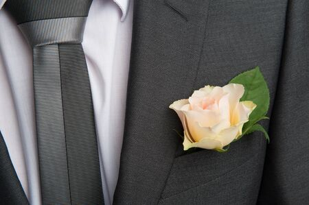 rose boutonniere flower on groom's wedding coat photo