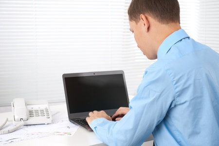 Rear view of a young business man working of a laptop photo