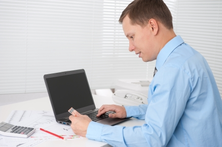 businessman paying online with his credit card at office photo