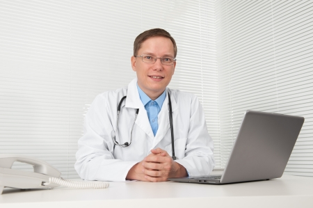 Doctor with laptop at desk in office photo