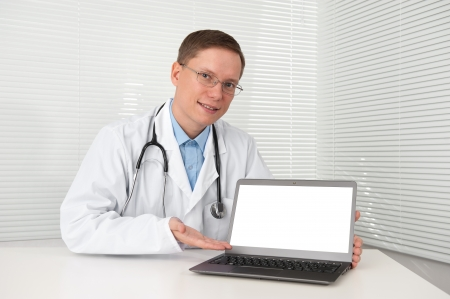 young doctor in lab coat with laptop photo