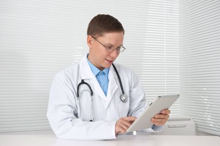 Smiling doctor with tablet computer in his office Stock Photo - 15100123