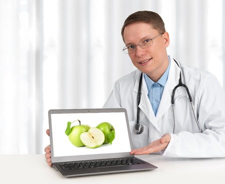 doctor showing green apples on his laptop computer Stock Photo - 15133484