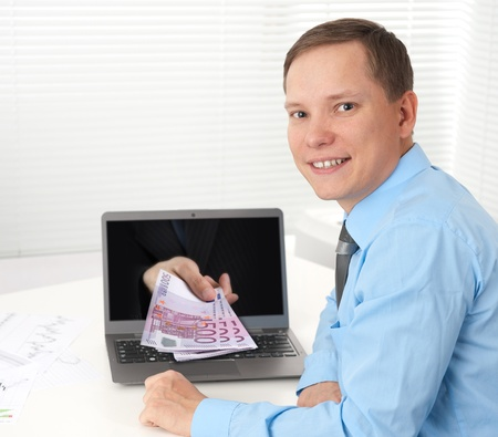 Human hand with money, coming out from the laptop computer screen Stock Photo - 15507572