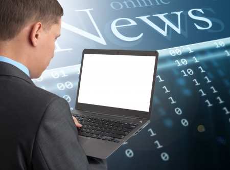 Businessman reading news at laptop computer photo