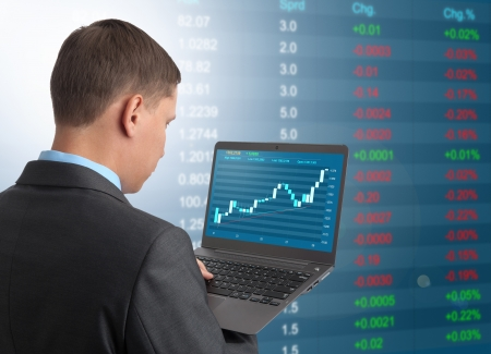 Businessman with laptop on Stock Market Background Stock Photo