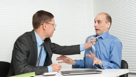 Business people fighting at the desk in office photo