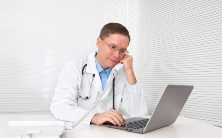 male doctor working on a laptop photo